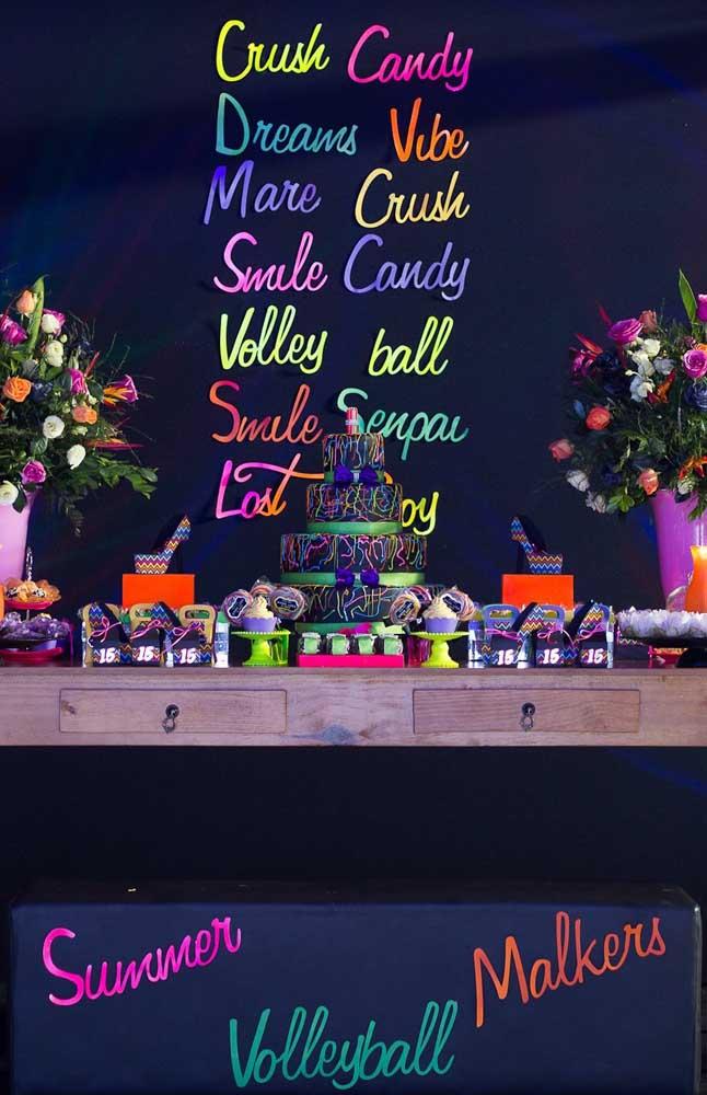 Mesa de doces da festa neon decorada com palavras nas cores da festa