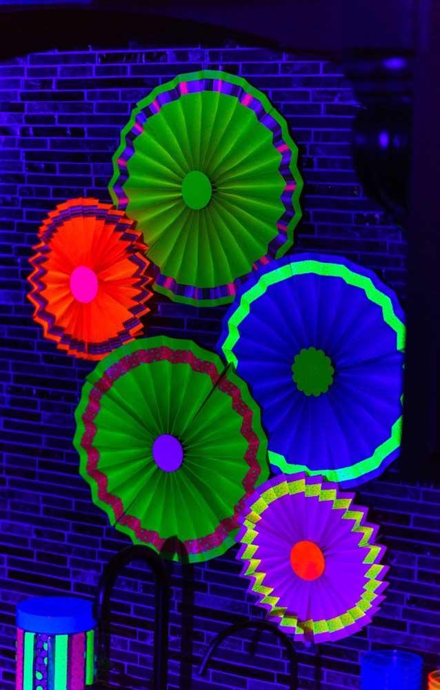 Aqueles simples enfeites de parede feitos com papel podem se tornar o destaque da festa neon, basta aplicar efeito de luz sobre eles