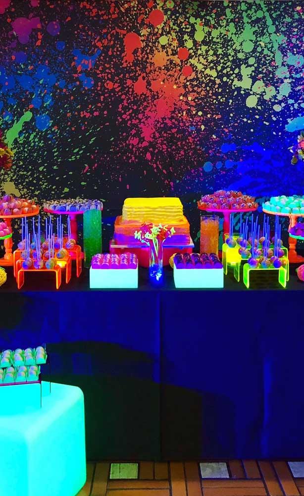 Essa festa neon traz como sugestão um painel borrado com tinta de diferentes tons