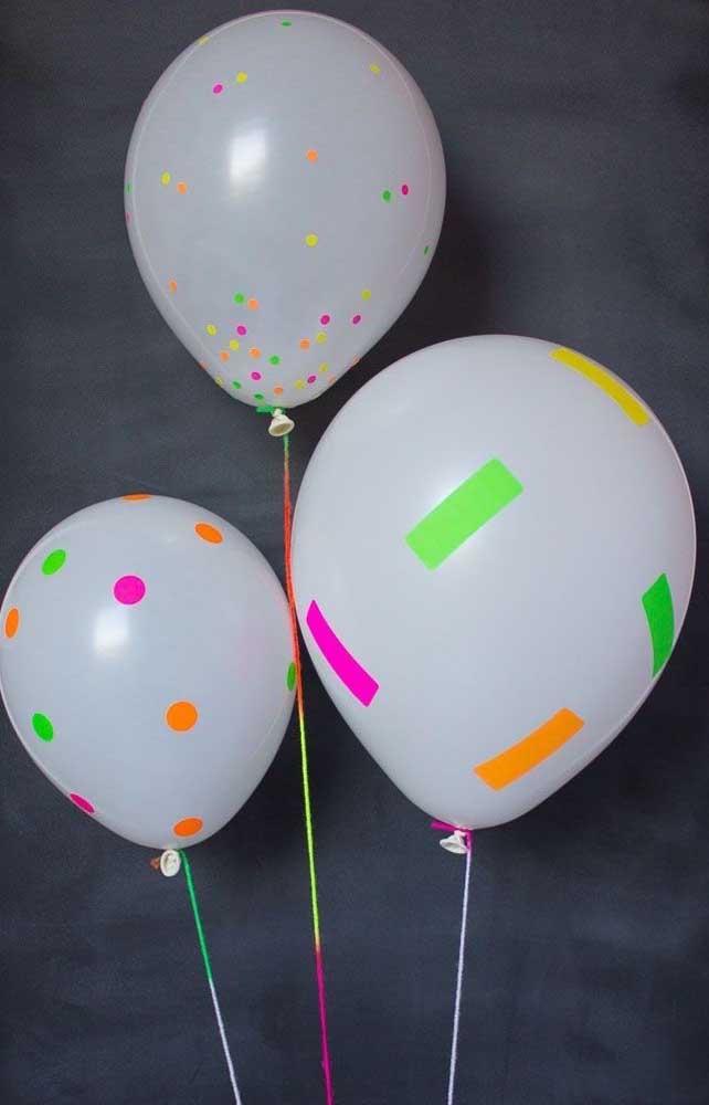 Os balões brancos, super simples, se tornaram a decoração da festa neon graças ao uso de fita adesiva sobre eles