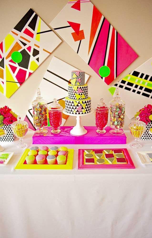 Sugestão de mesa de bolo para a festa neon; repare que os quadros aos fundos fazem a vez dos tradicionais painéis
