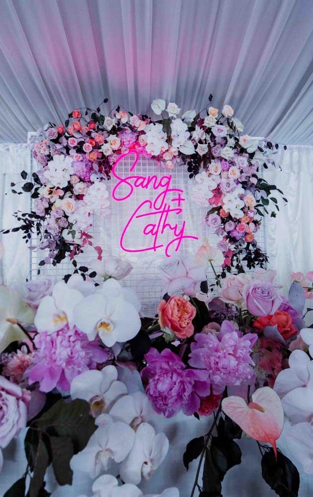 Festa neon decorada com flores e letreiro luminoso, item indispensável em festas desse tipo