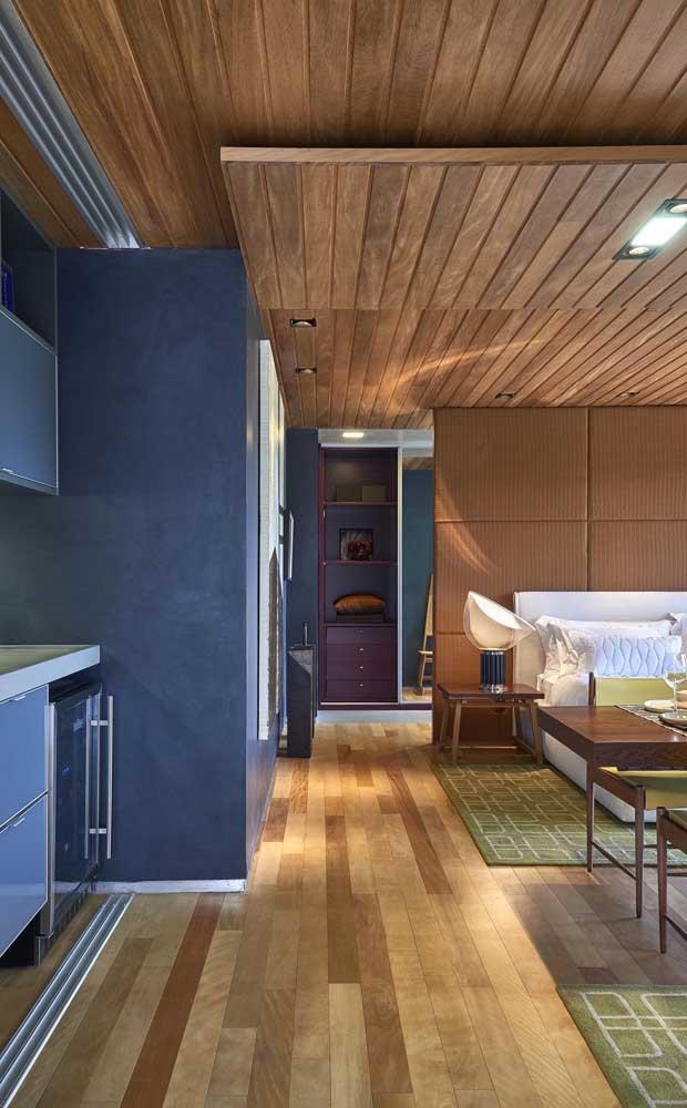 Forro de madeira sobreposto com iluminação embutida; no chão, a madeira também se destaca