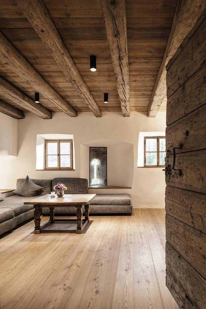 A rusticidade predomina nesse forro de madeira; repare na composição criada junto com a porta