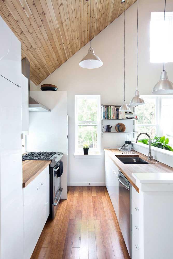 Já aqui, a cozinha branca é evidenciada pelo uso do forro de madeira em tom natural