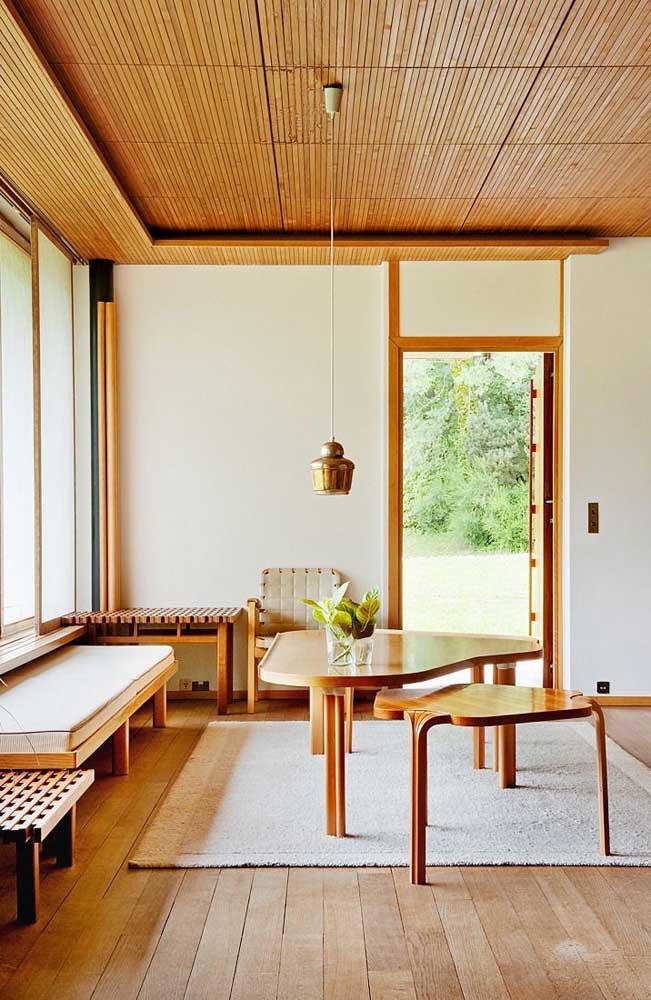 O pé direito alto da sala contou com um forro de madeira com lambris estreitos e moldura sobreposta semelhante a uma sanca de gesso