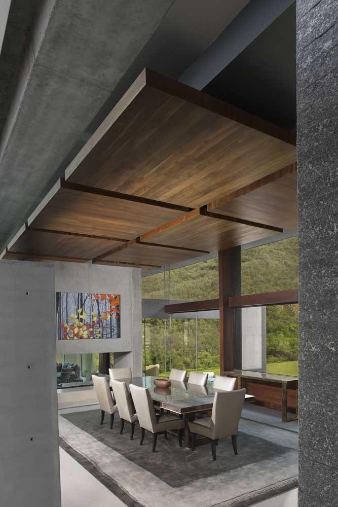 Nessa sala de jantar, a ideia do forro tradicional de madeira foi substituída por placas maiores de madeira sobrepostas ao forro de alvenaria convencional