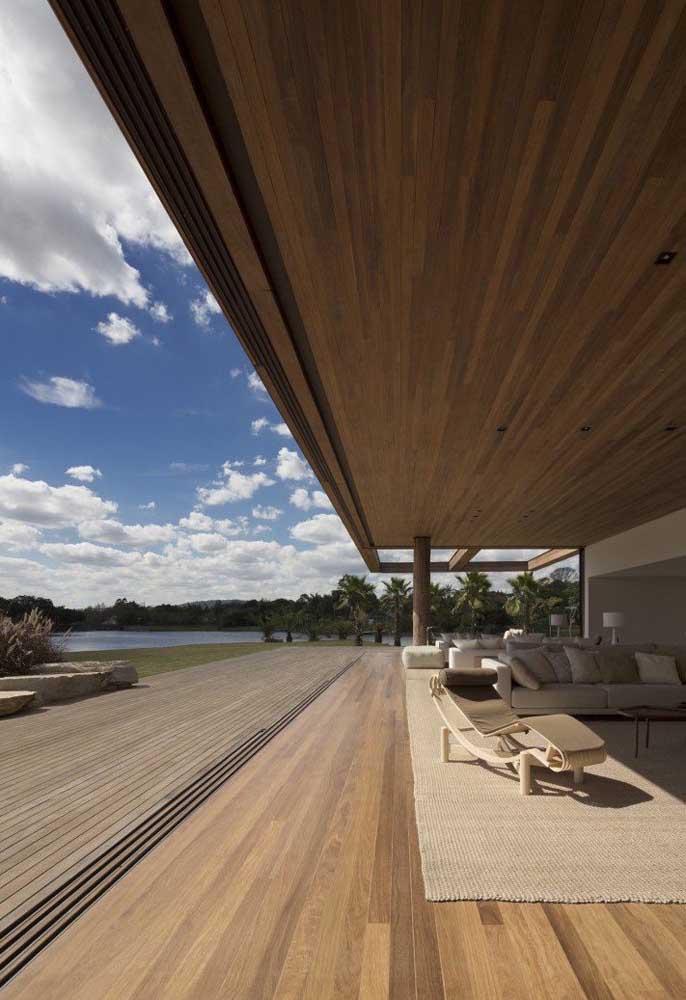 Amplo, alto e sofisticado, o forro de madeira junto ao piso é o destaque desse ambiente externo