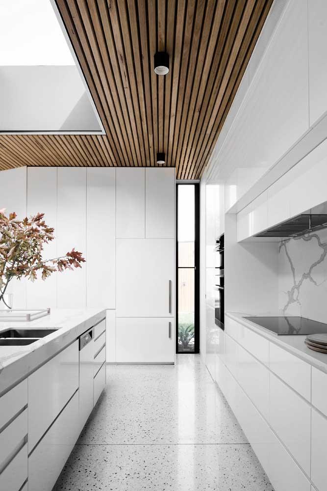 Lambris espaçados de madeira contornam o teto dessa cozinha moderna