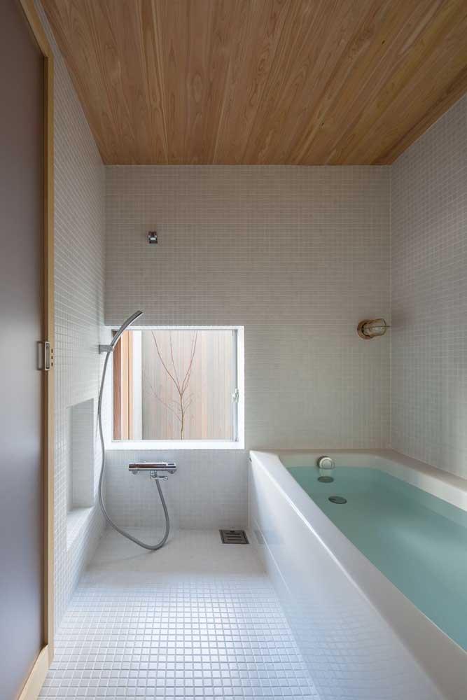 Para o banheiro clean, um forro de madeira clara instalado em placas