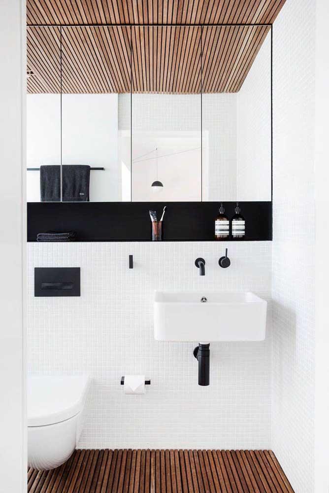 Nesse banheiro, o piso e o forro de madeira se harmonizam perfeitamente com os tons de branco e preto