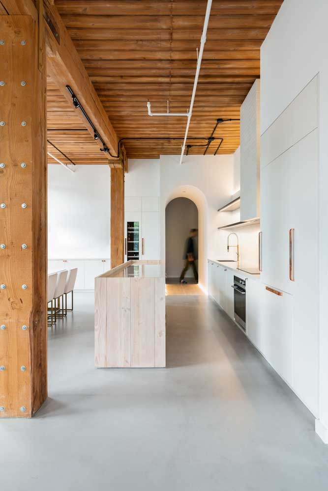 O forro de madeira rústico acompanha as vigas volumosas; repare ainda no contraste criado entre o tom da madeira e o branco do ambiente