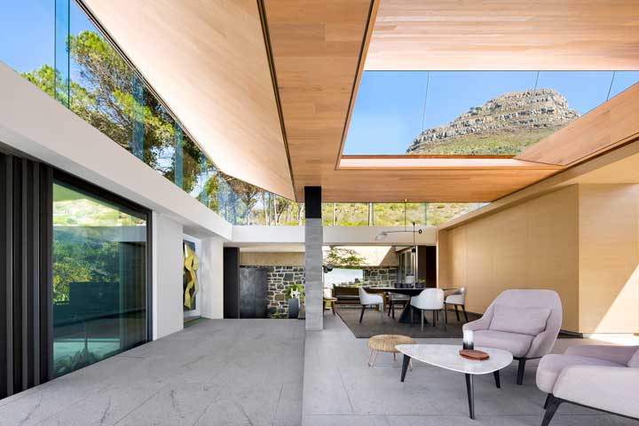 Uma casa contemporânea com forro de madeira instalado em placas intercalado pelas partes vazadas em vidro do telhado; lindíssima proposta!