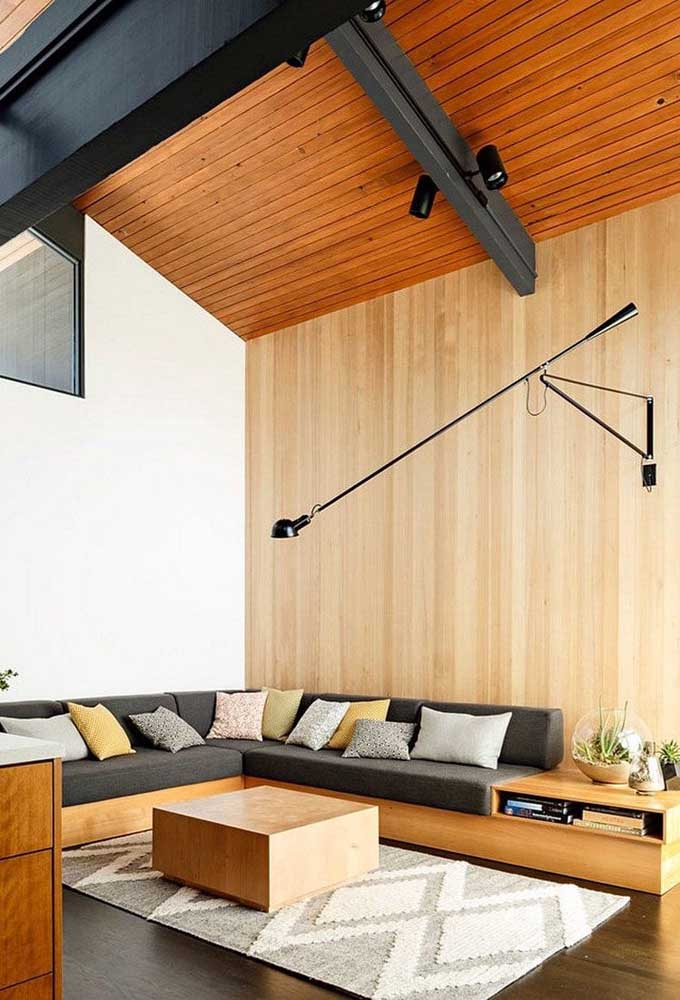 Três tons de madeira espalhados nesse ambiente: no forro, na parede e no piso