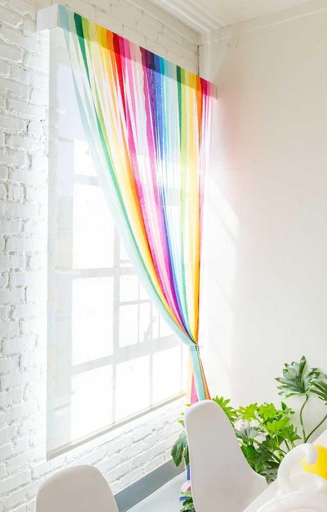 O ambiente todo branco ganhou uma cortina arco íris que é pura alegria