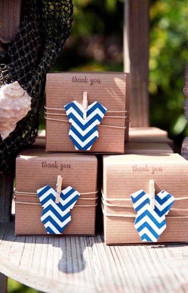Lembrancinhas de chá de bebê embrulhadas em papelão e decoradas com roupinha de papel