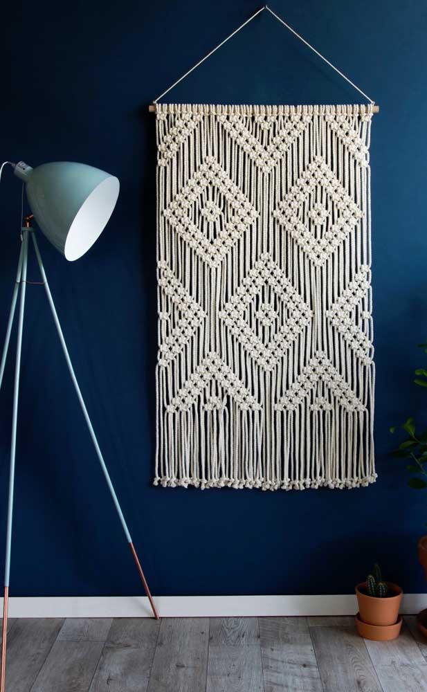 A parede azul dessa sala ajuda a destacar e valorizar o enfeite de parede feito em macramê cru