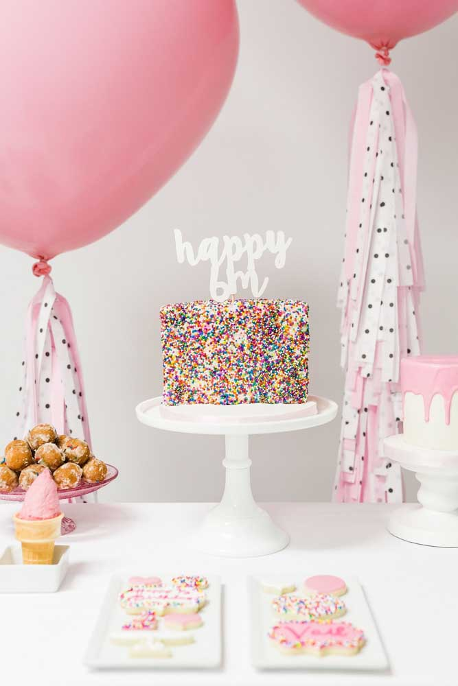 Sugestão de decoração para o mesversário em tons de rosa e branco; destaque para o bolo enfeitado com confeites coloridos