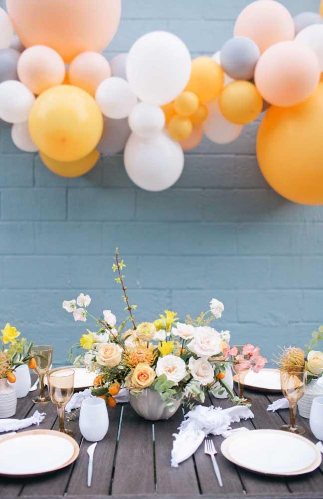 Mesversário de decoração rústica, feito ao ar livre; um almoço caprichado aguarda os convidados