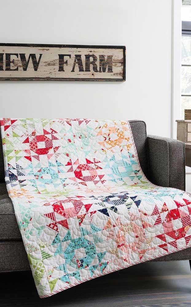 Colcha em patchwork que serve também como manta para sofá; repare na combinação harmoniosa de cores