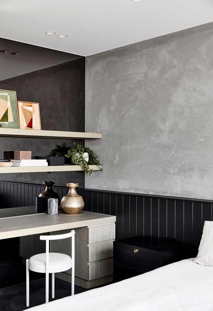 A parede feita de cimento queimado consegue ser o grande destaque do quarto.