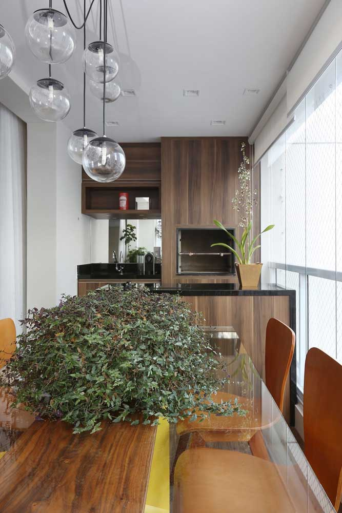 Varanda gourmet de apartamento com churrasqueira revestida em madeira