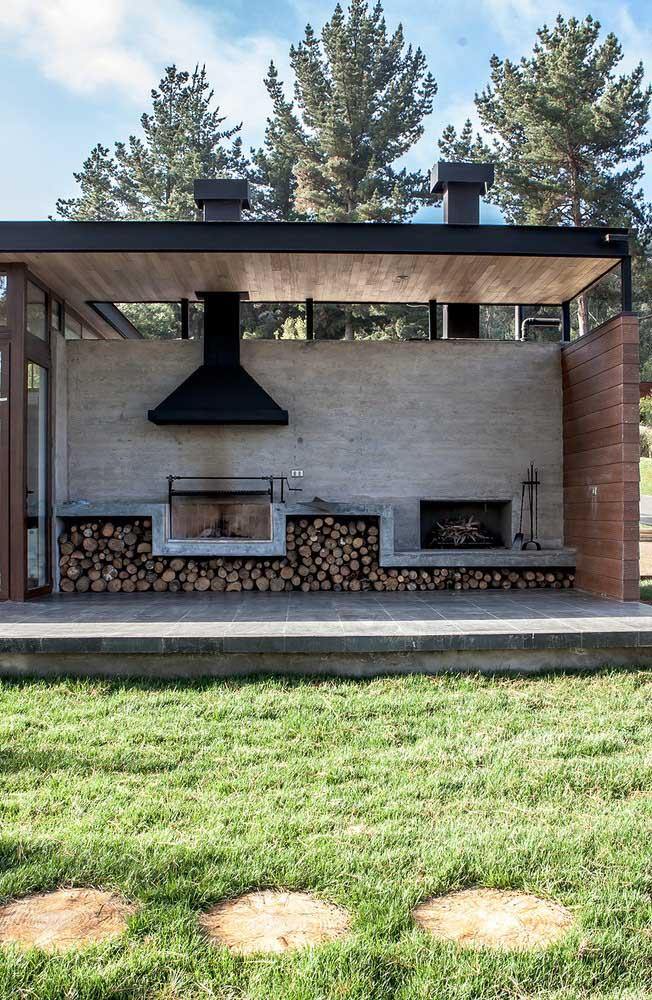 Um espaço gourmet de frente para o jardim, com churrasqueira revestida em pedra e alvenaria