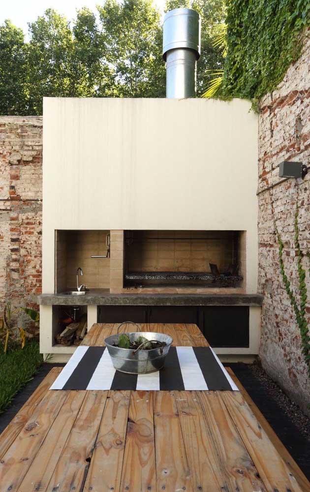 Para combinar com o estilo rústico do jardim, a churrasqueira foi revestida em alvenaria