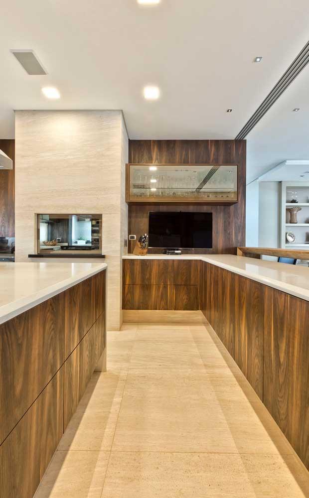 Para esse espaço gourmet elegante, os armários, paredes e bancadas foram revestidos com madeira, mas para a área da churrasqueira foi escolhido o porcelanato
