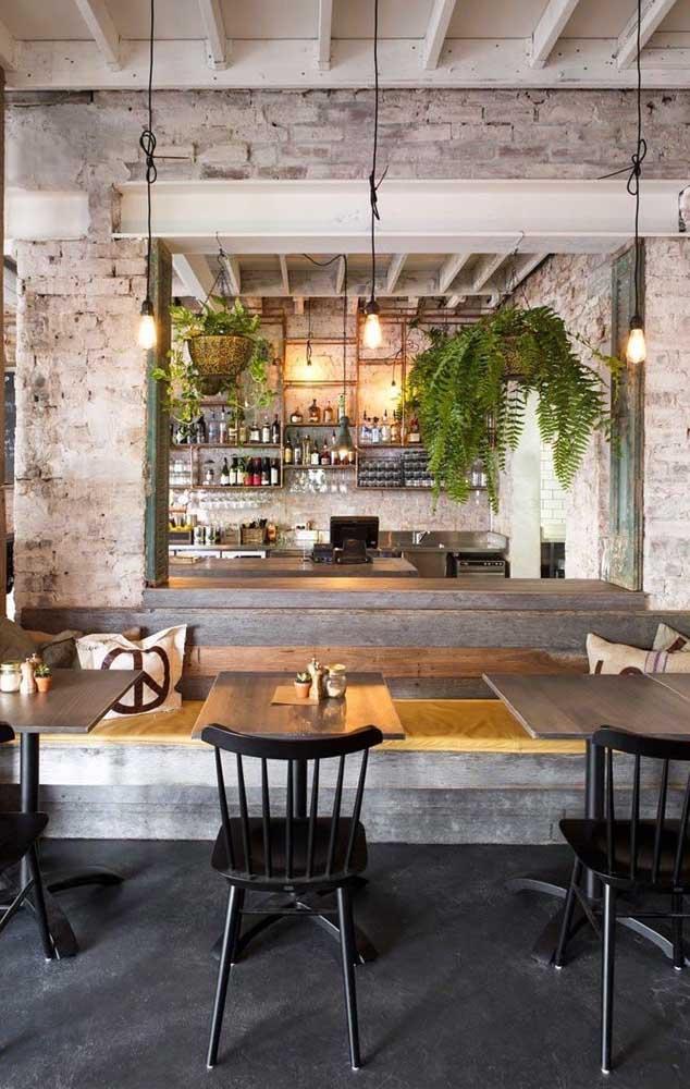 Essa cozinha americana apostou no uso de samambaias marcando a divisão entre os ambientes