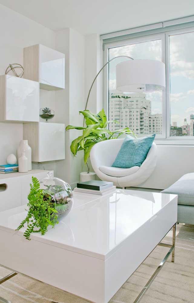 A sala branca, clean e moderna ganhou vida com o verde intenso das samambaias