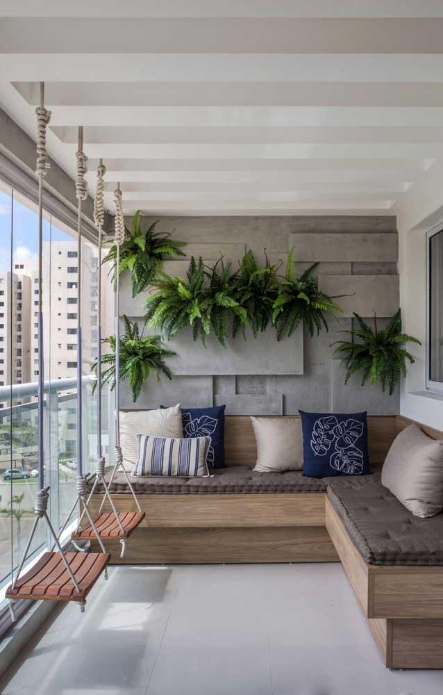 Jardim vertical na varanda do apartamento feito com samambaias