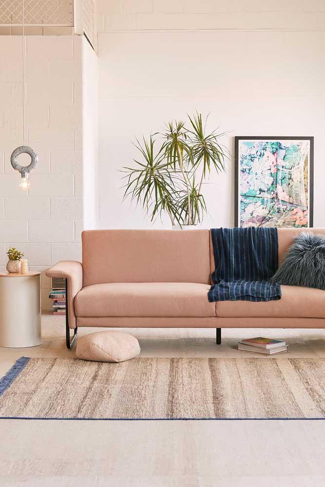 Sofá moderno em um tom suave de rosa; repare nas linhas retas que marcam o desenho da peça
