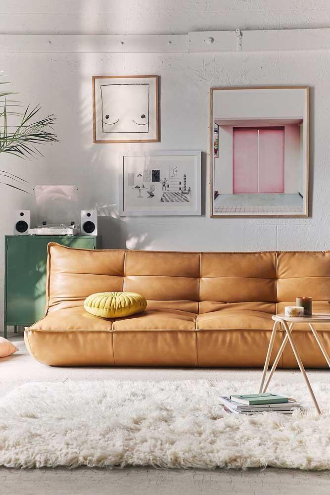 Sofá moderno de couro apoiado diretamente no chão; uma opção super aconchegante para salas de estilo descontraído e jovial