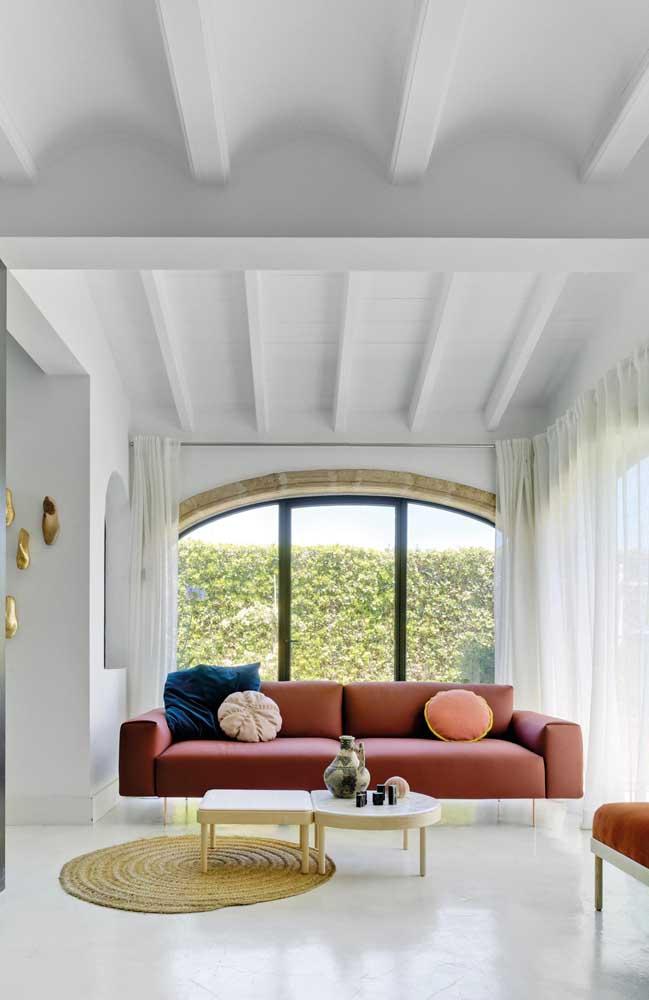 O tom de vermelho queimado desse sofá moderno é o ponto de maior destaque na sala branca
