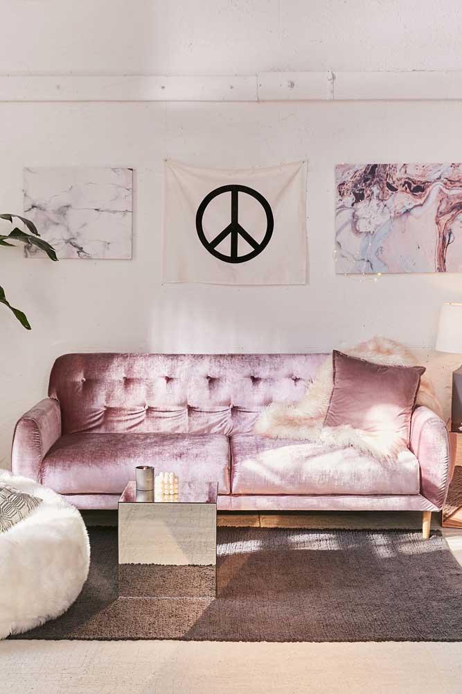 A sala de estar toda hipster apostou em um sofá de veludo cor de rosa com encosto em capitonê
