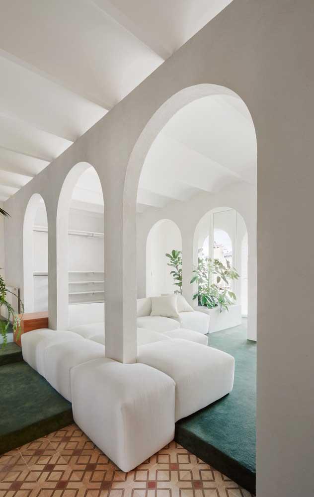 Essa sala de estar muito bem arejada e iluminada contou com um modelo de sofá moderno branco super clean