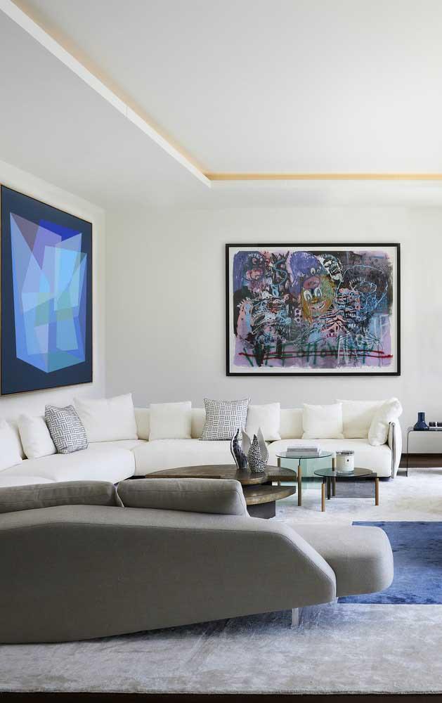 Já nessa sala ampla, a opção foi por um modelo de sofá moderno de canto que acompanha todo o contorno do ambiente