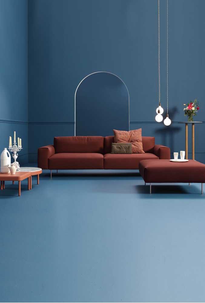 Uma sala de estar super conceitual com um sofá vermelho queimado de linhas retas combinando com o puff ao lado
