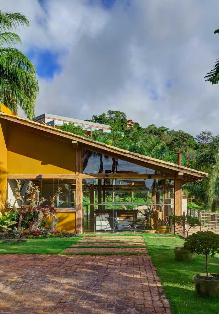 Casa térrea com telhado colonial meia água para a direita do terreno e estrutura em madeira à vista