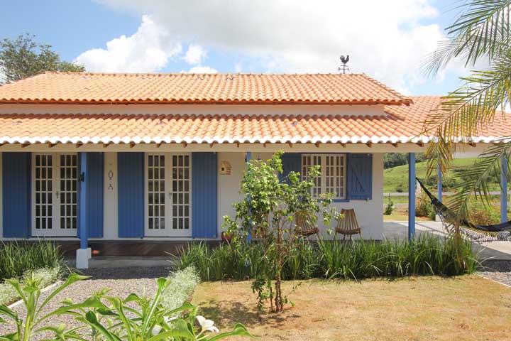 Casa rústica com telhado colonial ornando com os acabamentos das portas e janelas
