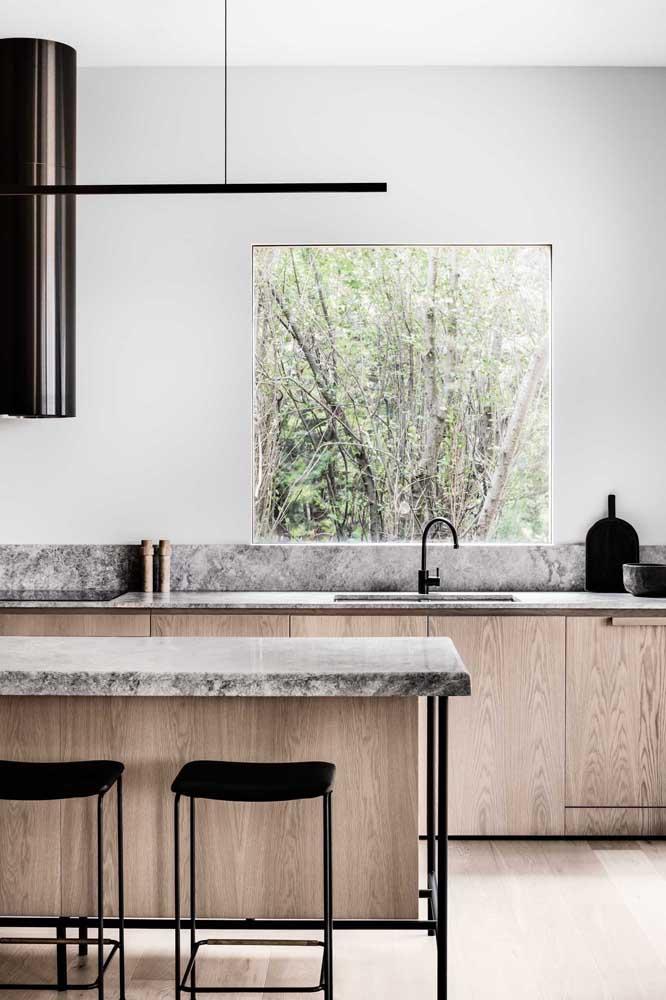 Essa cozinha moderna e iluminada investiu no granito cinza para a bancada e a ilha; os detalhes em preto garantem o charme final do projeto