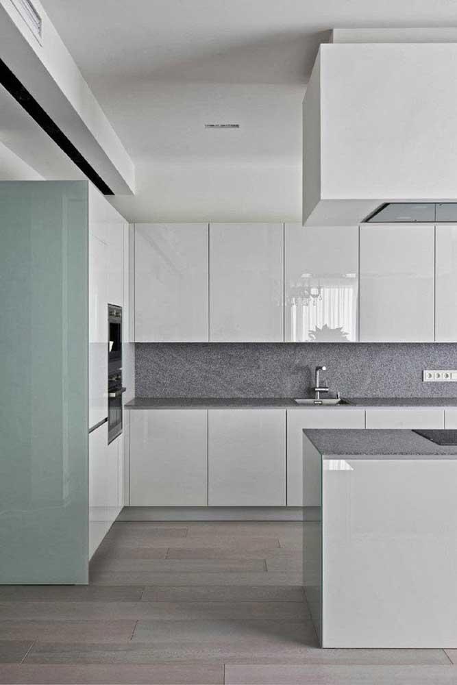 O granito cinza pode ser usado com sucesso em ambientes de base neutra, como nessa cozinha de armários brancos e piso de madeira clara