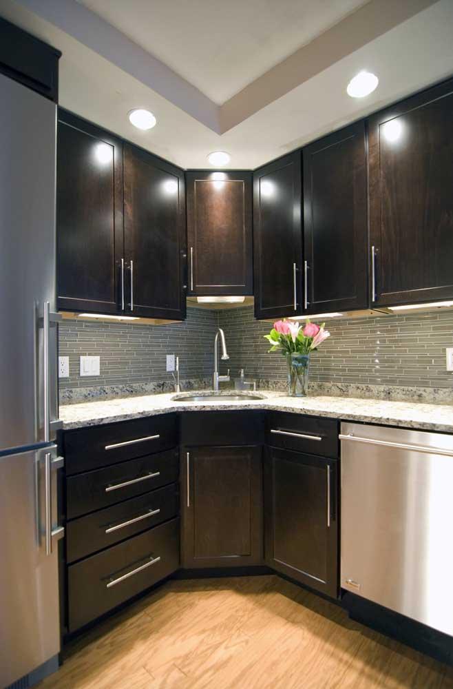 Modelo de cozinha de canto com bancada de granito; repare como a iluminação natural valoriza o projeto