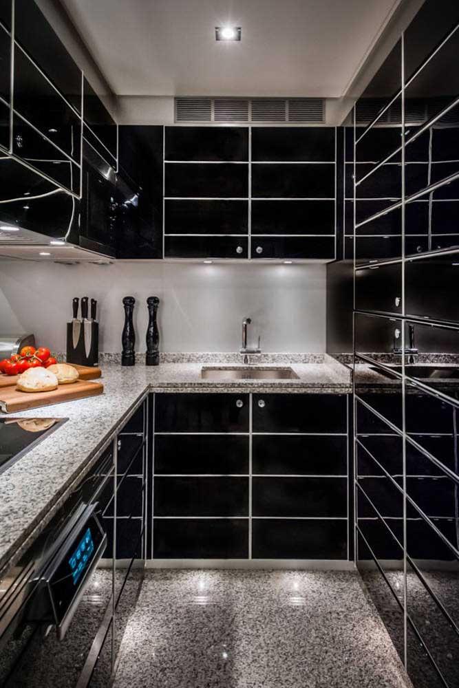 Essa cozinha pequena e toda preta optou por um granito cinza na bancada