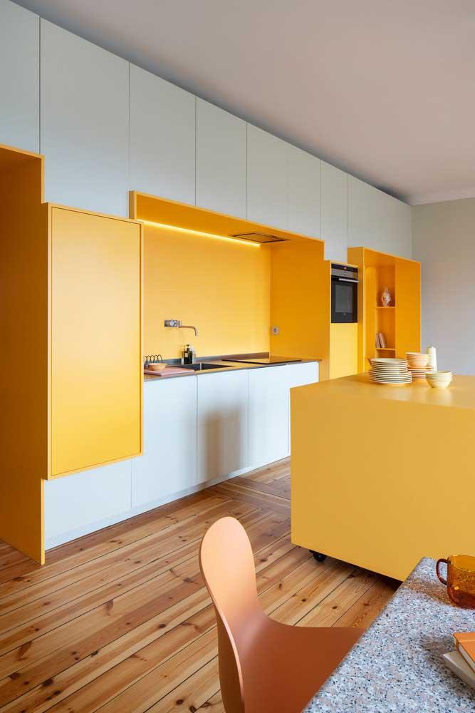 Uau! Que cozinha maravilhosa que faz a combinação das cores amarela, branca e piso de madeira.