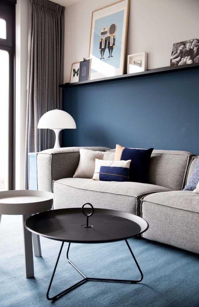 Na sala de estar, a meia parede azul confere elegância e charme para a decoração