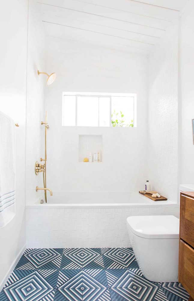 O banheiro clean e moderno apostou em um piso azul para trazer cor ao ambiente, sem, contudo, perder a neutralidade