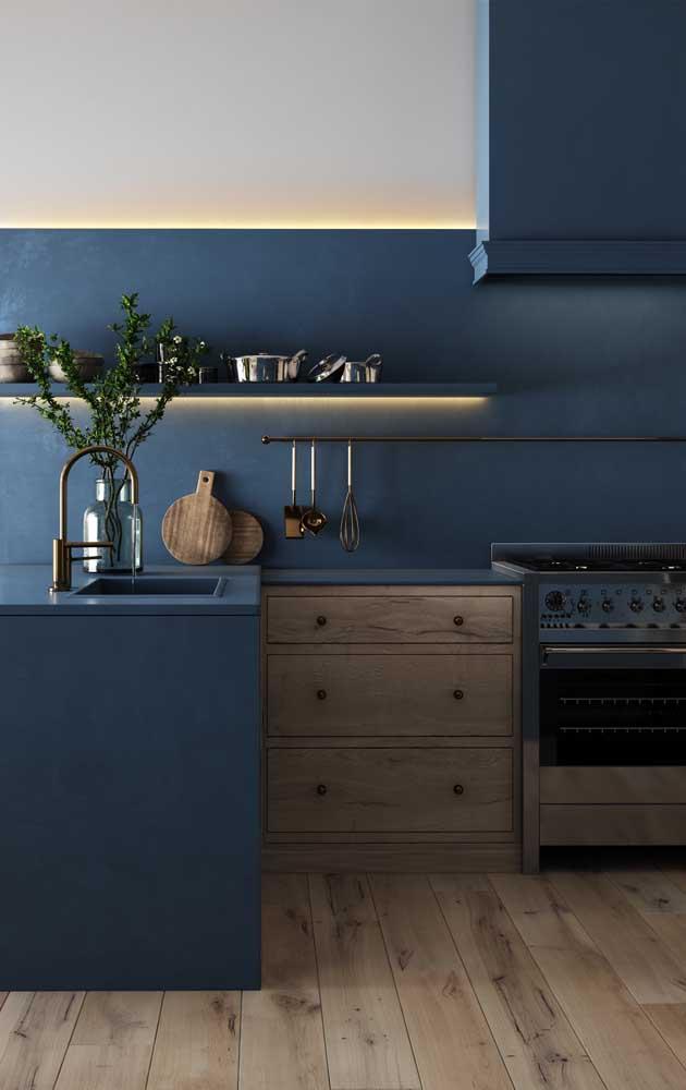 Nessa cozinha, o tom de azul petróleo ganhou ainda mais destaque com a faixa de LED instalada sob o nicho