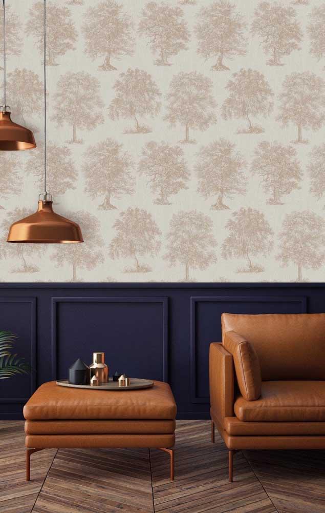 Nada como uma boiserie azul petróleo para sofisticar ao máximo uma sala de estar; as poltronas de couro caramelo vêm para reforçar a decor